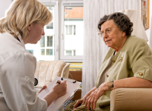 Nurse taking down Notes During Home Visit With Senior Couple Talking
